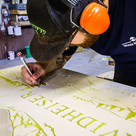 Our skilled craftsman engraving a custom design onto a headstone.